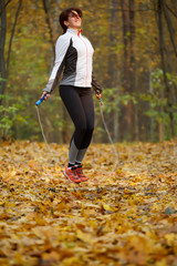 Side view of sporty woman jumping with rope at autumn forest