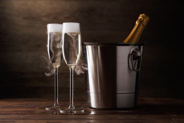 Image of two wine glasses with sparkling wine, iron bucket