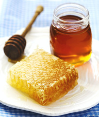Honeycombs with honey, honey in glass jar and wooden honey dipper on plate