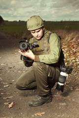 Photographer in war conflict field zone capturing video