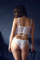 Beautiful woman with good body shape stands back in white lace lingerie.