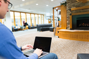 Male works on personal laptop in library