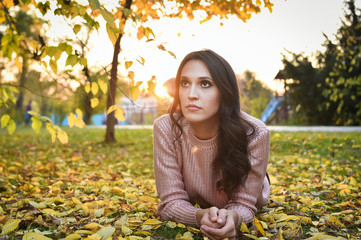 young woman lying down on the ground in a park in autumn