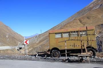 Stary wóz, stara przyczepa przy drodze na tle gór. Gruzja