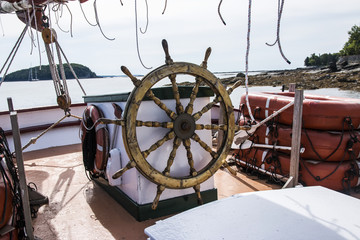 The helm of a wooden sailboat with porcupine island in the background