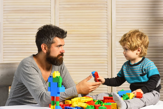Father and son with serious faces play with toy bricks