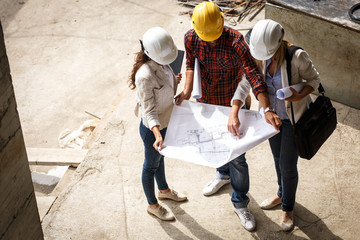Two female inspectors and architects discuss with head engineer about blueprints of construction site.