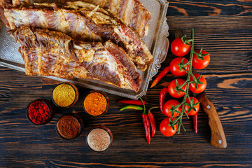 raw marinated pork ribs and tomatoes of garlic pepper on a black board