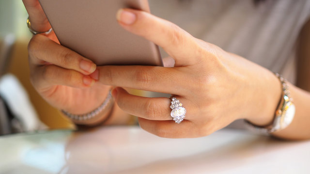 Woman hand close up on diamond ring using a mobile phone. (Selected focus)