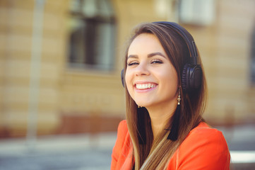 Fashion smiling woman listening to music on headphones, colorful red jacket against the backdrop of a European city