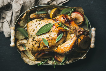 Oven roasted whole chicken with onion, apples and sage in serving tray over dark stone background, top view, selective focus. Celebration food concept