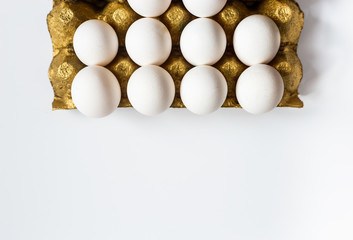 Fresh eggs on a gold support, stand in a row on a white background. Place for your advertizing text