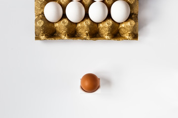 Fresh eggs on a gold support, stand in a row on a white background. Business concept of the leader
