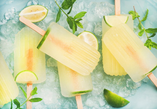 Summer refreshing lemonade popsicles with lime and mint with chipped ice over blue background, top view