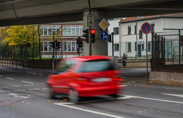 Verkehrsdelikt Rotlichtverstoß rotes Auto fährt bei Rot über eine Ampel - Red light offence Red car drives over a traffic light at red light