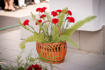 A bouquet of red carnations and fern in the wicker basket on the street
