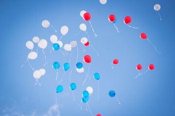 Balloons of red blue and white colors flying in the blue sky with clouds