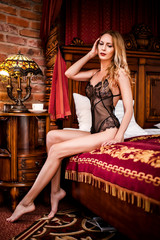 beautiful woman in a trendy black lace body sitting on a chic bed