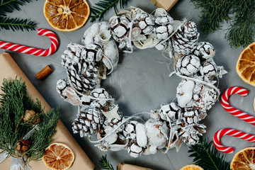 Christmas background with a wreath, candy and gifts on a gray background