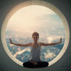 Beautiful sporty fit yogi woman practices yoga asana Padmasana - Lotus pose in a round window