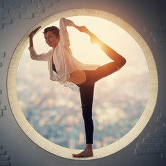 Beautiful sporty fit yogi woman practices yoga asana Natarajasana - Lord Of The Dance pose in a round window at sunset