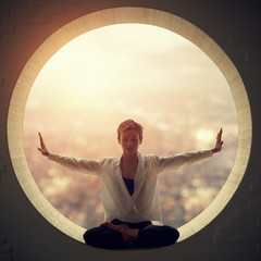 Beautiful sporty fit yogi woman practices yoga asana Padmasana - Lotus pose in a round window