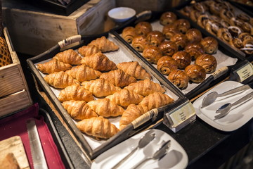 Croissants on a wooden tray in the buffet line