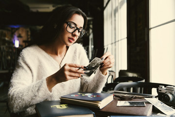 Woman looks at old photots sitting in a cosy cafe
