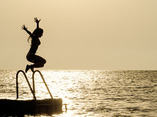 Silhouette of a girl against the sky jumping in the sea on the sunset, concept of happiness