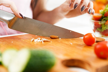 Woman cuts almonds on the wooden board