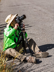 Photographer in a green jacket, white hat and boots takes a picture while sitting on the ground. The camera is on a tripod.