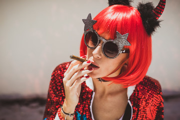Beautiful girl devil sitting on white background and smoke cigar. In anticipation of Halloween. Closeup Portrait. Wears black sunglasses