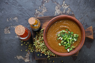 Pea soup with curry served in a clay bowl, top view on a brown stone background, horizontal shot