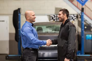 mechanic and customer shaking hands at car service