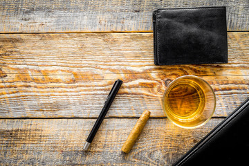 Drink whiskey in the evening. Glasses, wallet, cigar on rustic wooden background top view copyspace