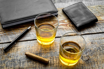 Drink whiskey in the evening. Glasses, wallet, cigar on rustic wooden background