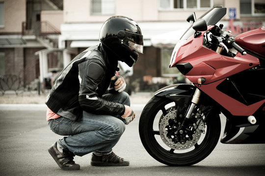 a guy a motorcyclist in a helmet and a leather jacket and jeans sits opposite a motorcycle of a sports red color and look him face to face