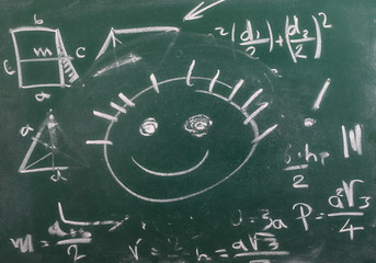 Mathematical equation and smiley face on chalkboard, blackboard texture