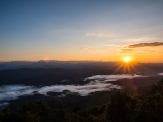 Sun rises above the long range of hills and white fog at Doi Samer Dao, one of the best location to see the fog in Nan, Thailand