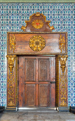 Closed wooden engraved aged door framed by golden ornate wooden frame on Turkish ceramic tiles wall with floral blue patterns, Mosque of Manial Palace of Prince Mohammed Ali Tewfik, Cairo, Egypt