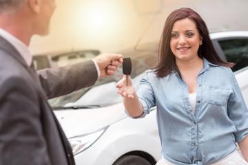 Car salesman handing car keys to young woman, light effect