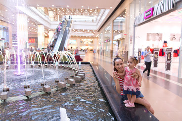 Mother and baby girl in a shopping center at the fountain