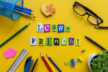 Word LEARN FRENCH made with carved letters on yellow desk with office or school supplies, stationery. Concept of Franch language courses