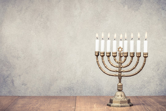 Bronze Hanukkah menorah with burning candles on wooden table front old vintage concrete wall background. Holiday greeting card concept. Retro instagram style filtered photo