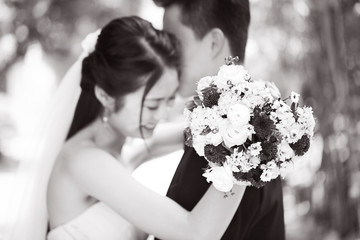 loving asian newly-wed couple, focus on the bouquet