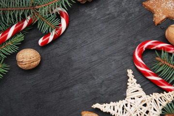 Christmas winter background. Black board with decorations in the corner. fir branches, candy sticks, nuts and decorative star, top view.