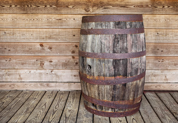 A vintage empty alcahol wooden keg sitting on a wood plank floor against a wood board wall