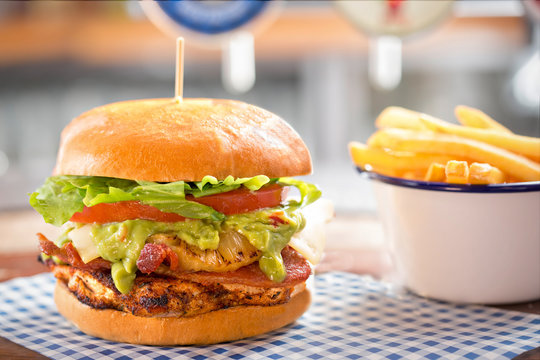Grilled chicken burger with bacon, guacamole, pineapple, cheese, lettuce & mayo