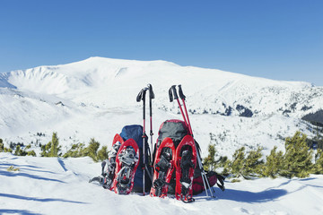 Backpacks stand in the snow against the backdrop of the mountains.