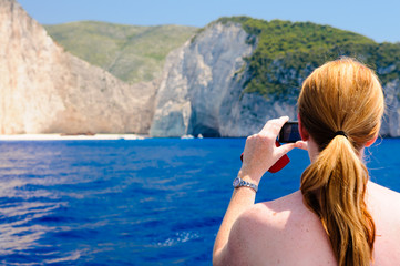 A woman takes a photograph f the shipwreck at Naviago Bay, Zante, Zakynthos